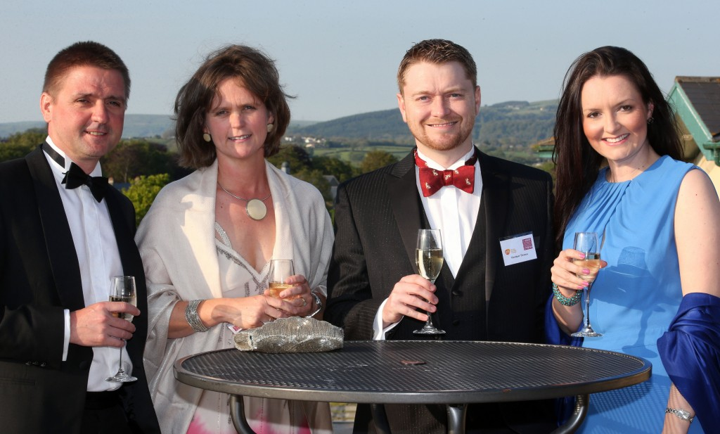 Four smiling people gathered around a table holding up glasses of champagne.