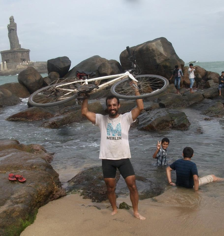 A man standing at the shore holding a bike over his head.