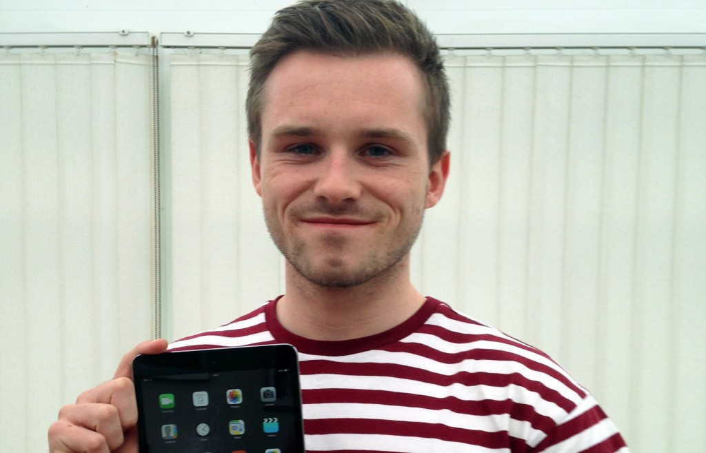 Portrait shot of a person with short hair holding an iPad and smiling into the camera