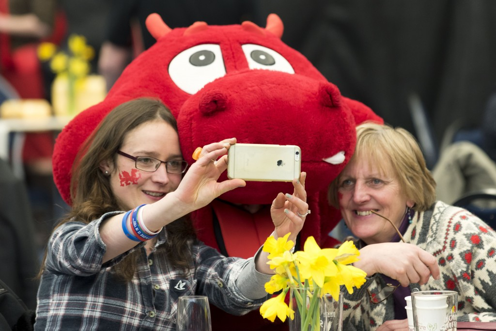 Two ladies taking a photograph with Dylan the Dragon (Photo by Matthew Horwood)