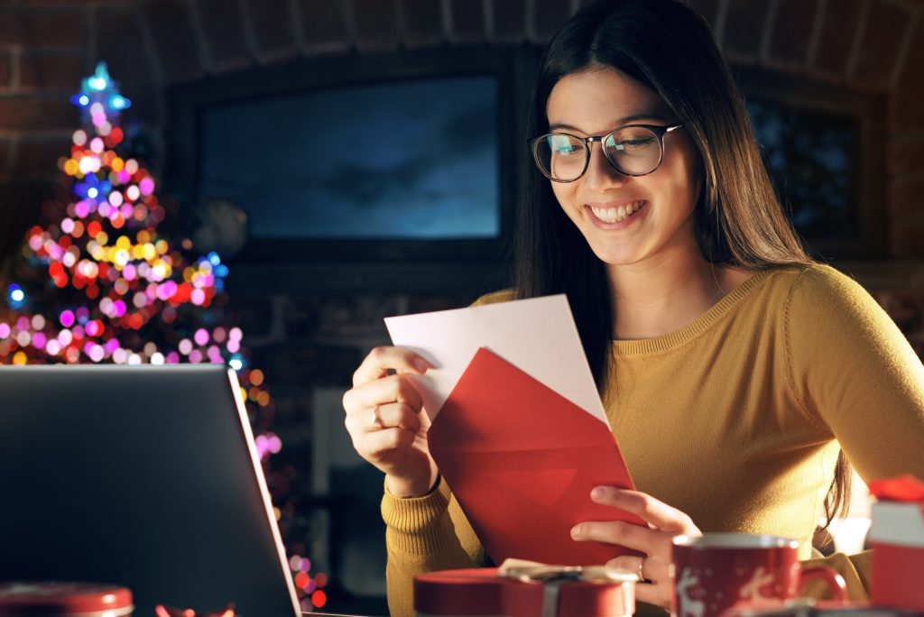 Young woman holding an envelope with a Christmas card