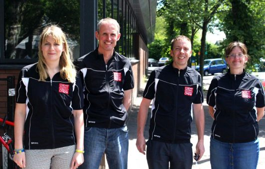 Two men and two women standing in a row smiling and wearing matching black shirts.