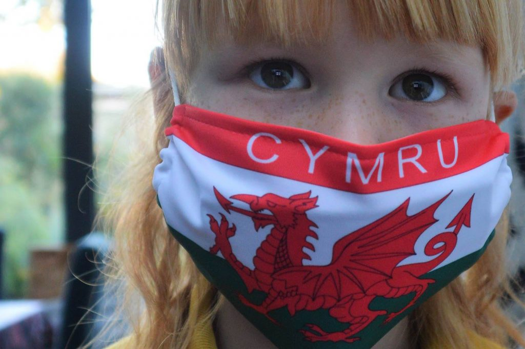 Girl wearing a mask bearing the Welsh flag.