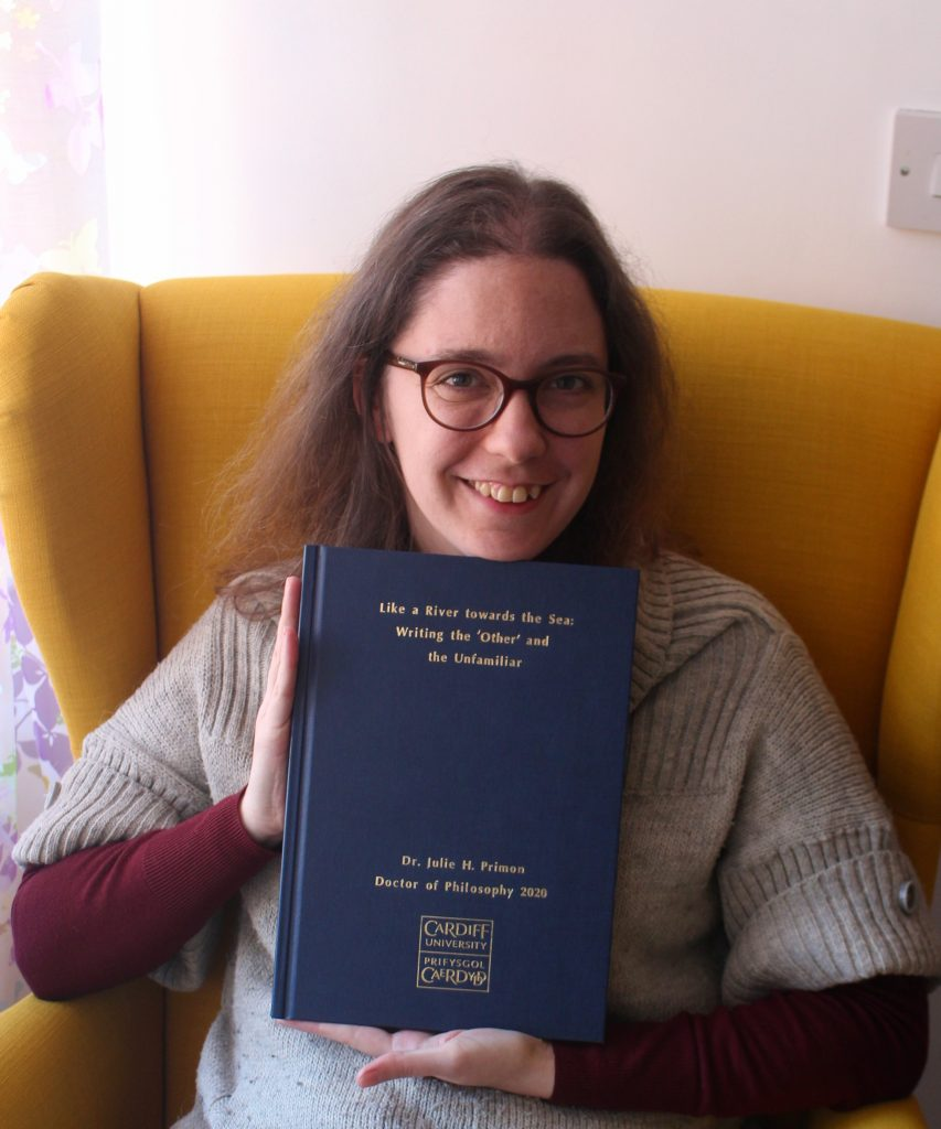 Julie showing her completed, bound thesis to the camera.