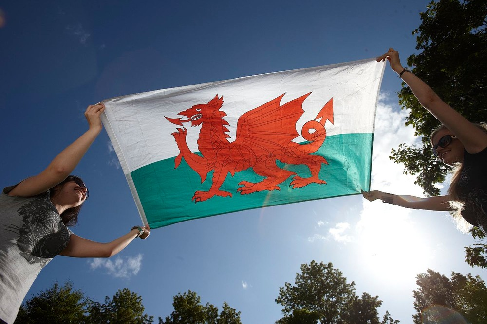 two young students holding a welsh flag