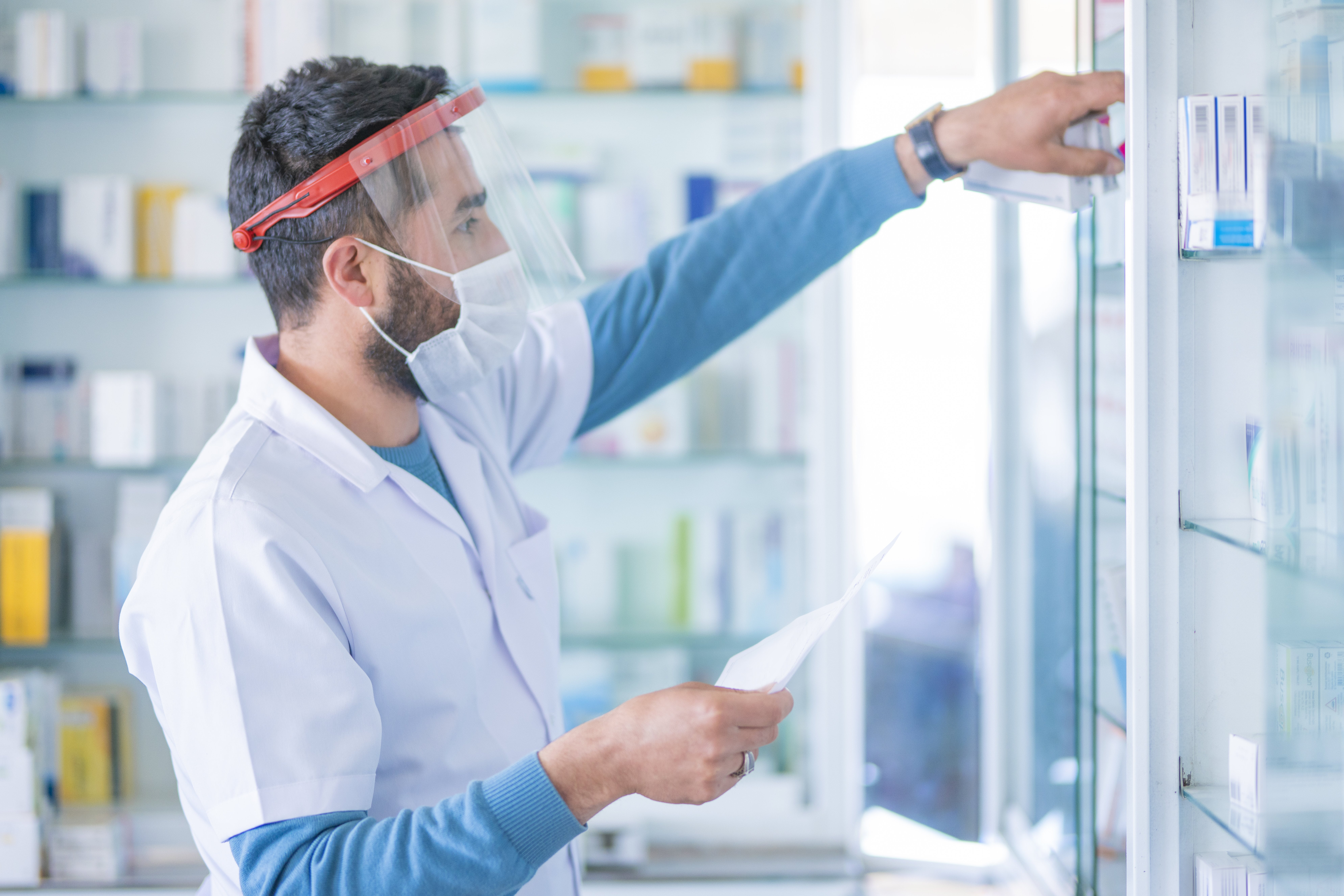 Pharmacist wears protective mask at work gives prescription medicine