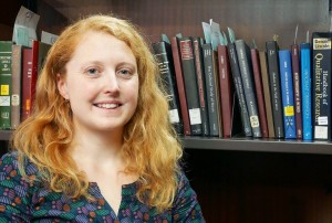 Woman with long red hair standing in front of a bookshelf and smiling into the camera.