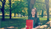 Charlotte standing in the park holding her dissertation.