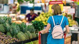 Woman standing beside fruit
