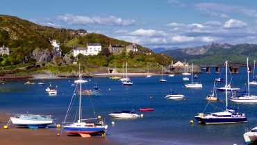 Picture of Barmouth with boats in the foreground and Barmouth Bridge in the background.